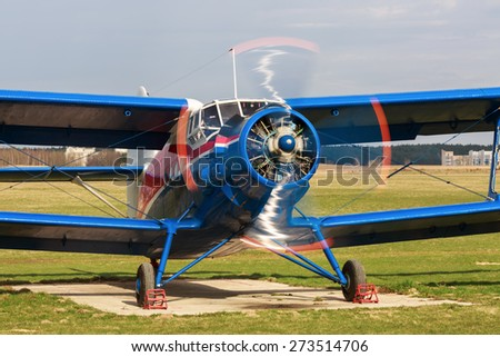 Old bright blue airplane with a rotating propeller close-up. Front view. Clear sunny day. - stock photo