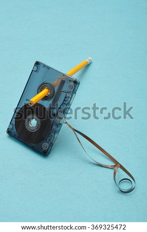 Old broken cassette  that was used for recording music on the isolated against a blue background - stock photo