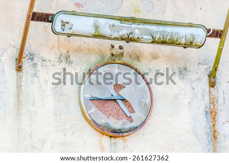 Old broken clock on industrial wall. Cover is broken and time has stopped. Place for text beside clock. Fluorescent light above clock is also broken. - stock photo
