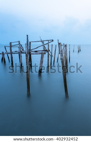 Old broken pier during awesome at evening. Blue tone color. Soft focus due to long exposure