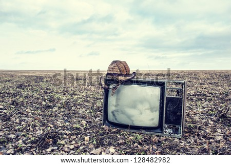old broken TV with hat is an autumn field - stock photo