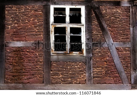 Old broken window in the wall of an old house - stock photo