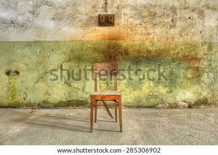 Old, broken, wooden chair against a filthy wall in an abandoned prison. Ready for interrogation.