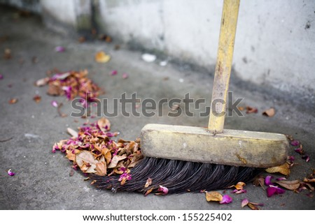 Old broom and flowers - stock photo