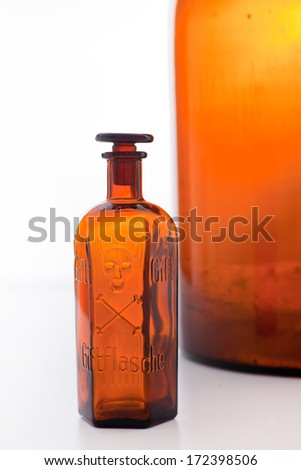 Old brown glass poison bottle with a stopper and an engraved skull and crossbones warning of the danger of the contents alongside a larger bottle on a white background - stock photo