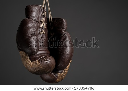 Old brown leather boxig gloves on dark gray background - stock photo