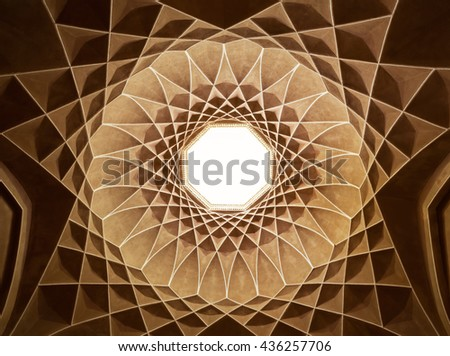 Old brown plasterwork with geometric Persian design inside dome of Governor Pavilion at Dolat Abad Garden of Yazd. - stock photo