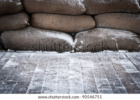 Old brown sandbags on snow covered wooden floor, taken on a winter morning. - stock photo