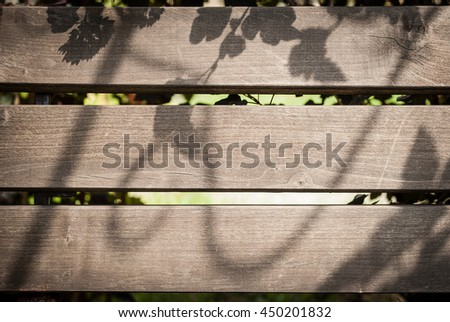 Old Brown wood plank with shadow over them from plants wall texture background