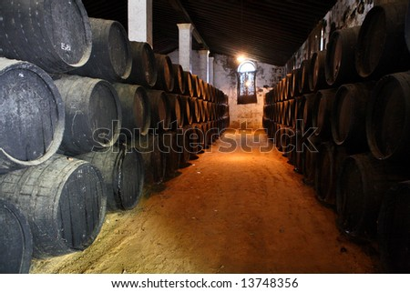 old brown wooden barrels of sherry in bodega of Spanish town of Jerez de la Frontera - stock photo