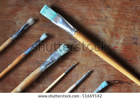 Old brushes on a wooden table