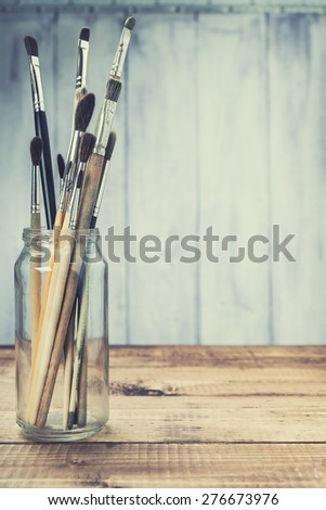 Old brushes on wooden background. Toned. - stock photo