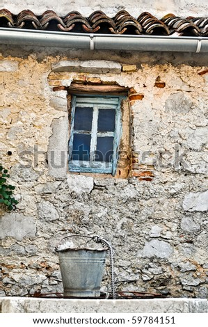 Old bucket above draw well in front of old building with lattice window. - stock photo