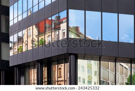 Old building architecture reflected in modern building. Front view of the building. Munich, Germany.