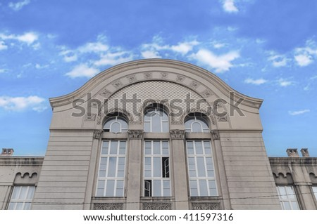 Old building detail with blue cloudy sky - stock photo