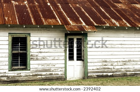 Old building in Breaux Bridge, Louisiana, with a rusted tin roof. - stock photo