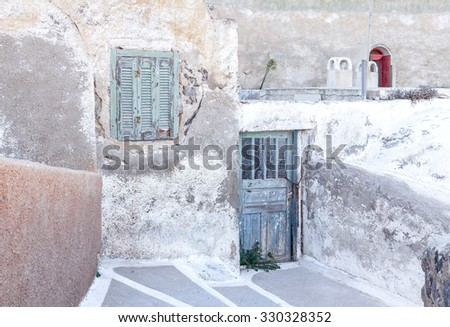 Old building with damaged wall, wooden window and door, vintage style - stock photo