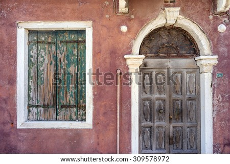 Old building with vintage of entrance door and window with shutters in European city - stock photo