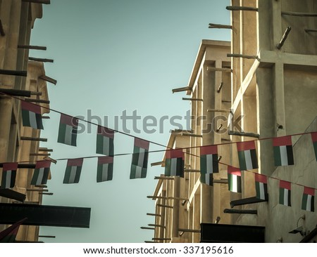 Old buildings in Dubai are decorated with bunting of UAE national flag. - stock photo