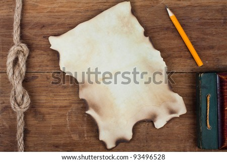 Old burnt paper and pencil on wooden background - stock photo