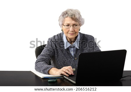 Old business woman reading stock news on the laptop screen