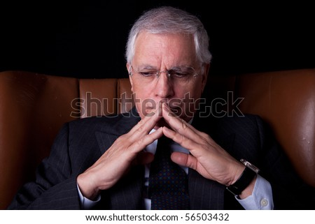old businessman  seated on a chair, thinking, isolated on black background, Studio shot - stock photo
