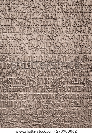 Old byzantine writing at stone texture. Ancient textured background with slavonic text and signs on the wall.