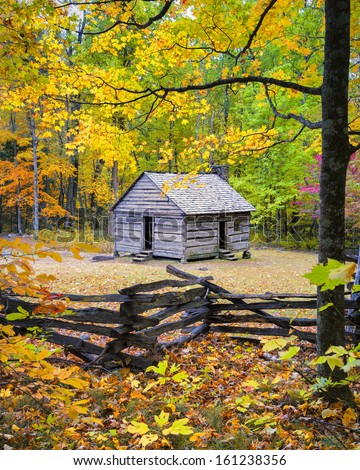 Old cabin framed by colorful fall foliage on Roaring Fork Road, Smoky Mountains National Park - stock photo
