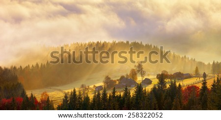 old cabin in the fog, and all lit amber - stock photo
