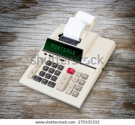 Old calculator showing a text on display - mortgage - stock photo