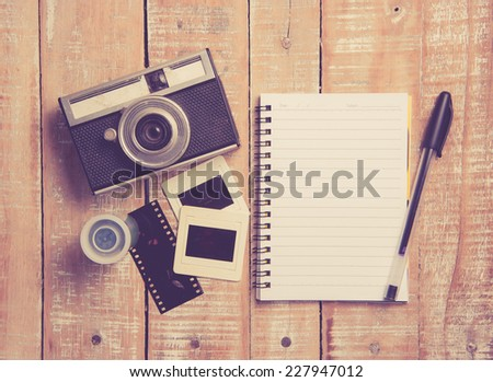 Old camera and film with diary on a wooden,vintage color toned image - stock photo
