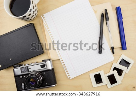 Old camera,cup of coffee, blank note, pen and transparency slides - stock photo
