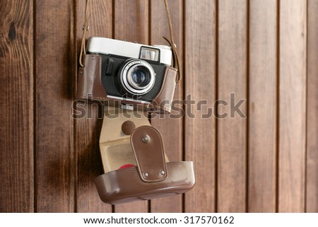 old camera hanging on wooden wall