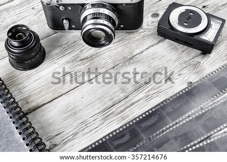 Old camera, negative film strip and exposure meter on the table  - stock photo