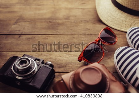 Old camera, sunglasses and sneakers on a wooden floor background.  Free space for text.  - stock photo
