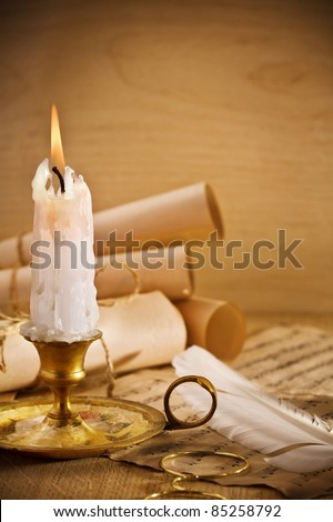 old candle on table with rolls of paper
