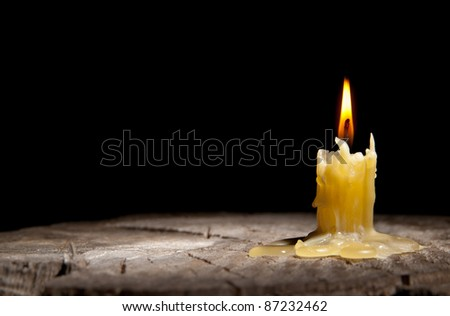 old candle stands on the stump of a tree on the black background - stock photo