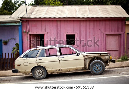 old car in front of pink building