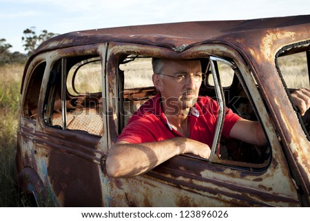 Old car, man in his 50's behind the wheel of a rusted out, vintage type car in an Australian field. - stock photo