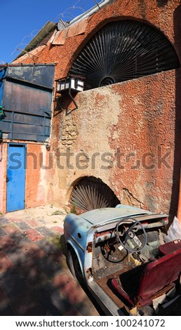 Old car on the grunge building wall background - stock photo