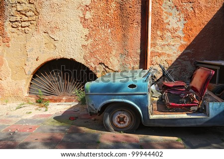 Old car on the grunge wall background - stock photo