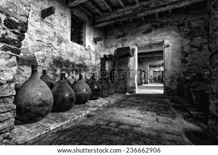 Old carboys in a very old house without doors. - stock photo