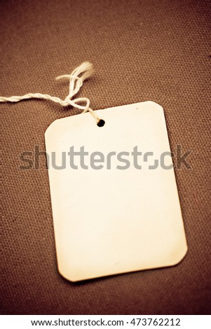 Old card tag on a textured surface.