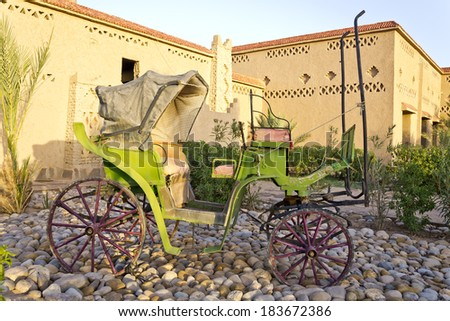 Old carriage standing on a garden in the desert  - stock photo