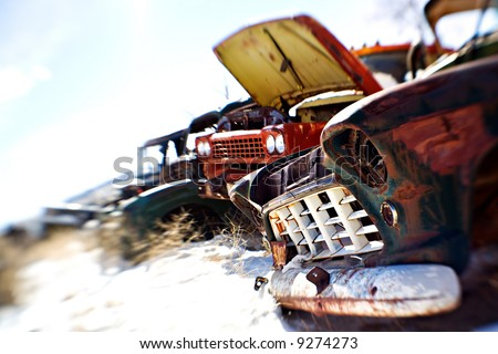 old cars in the snow at a rural junkyard. shot with a lensbaby - limited depth of field with focus on front grill. legal note - license plate heavily modified. - stock photo