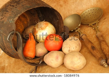 Old casserole with vegetables and kitchen utensils - stock photo