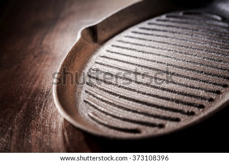 Old cast iron griddle pan for roasting and grilling in a close up angled view on a rustic wooden table - stock photo