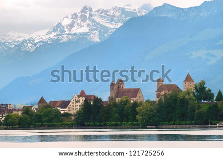 Old castle on Zurich lake with Alps mountains in background, Switzerland - stock photo