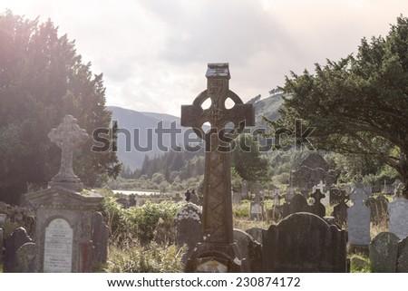 Old Celtic Cross in The Glendalough s Cemetery. Wicklow mountain, Ireland - stock photo