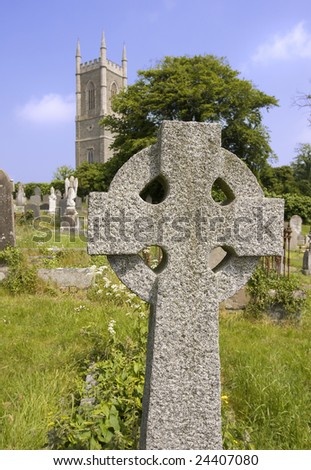 old celtic cross with church and steeple in background